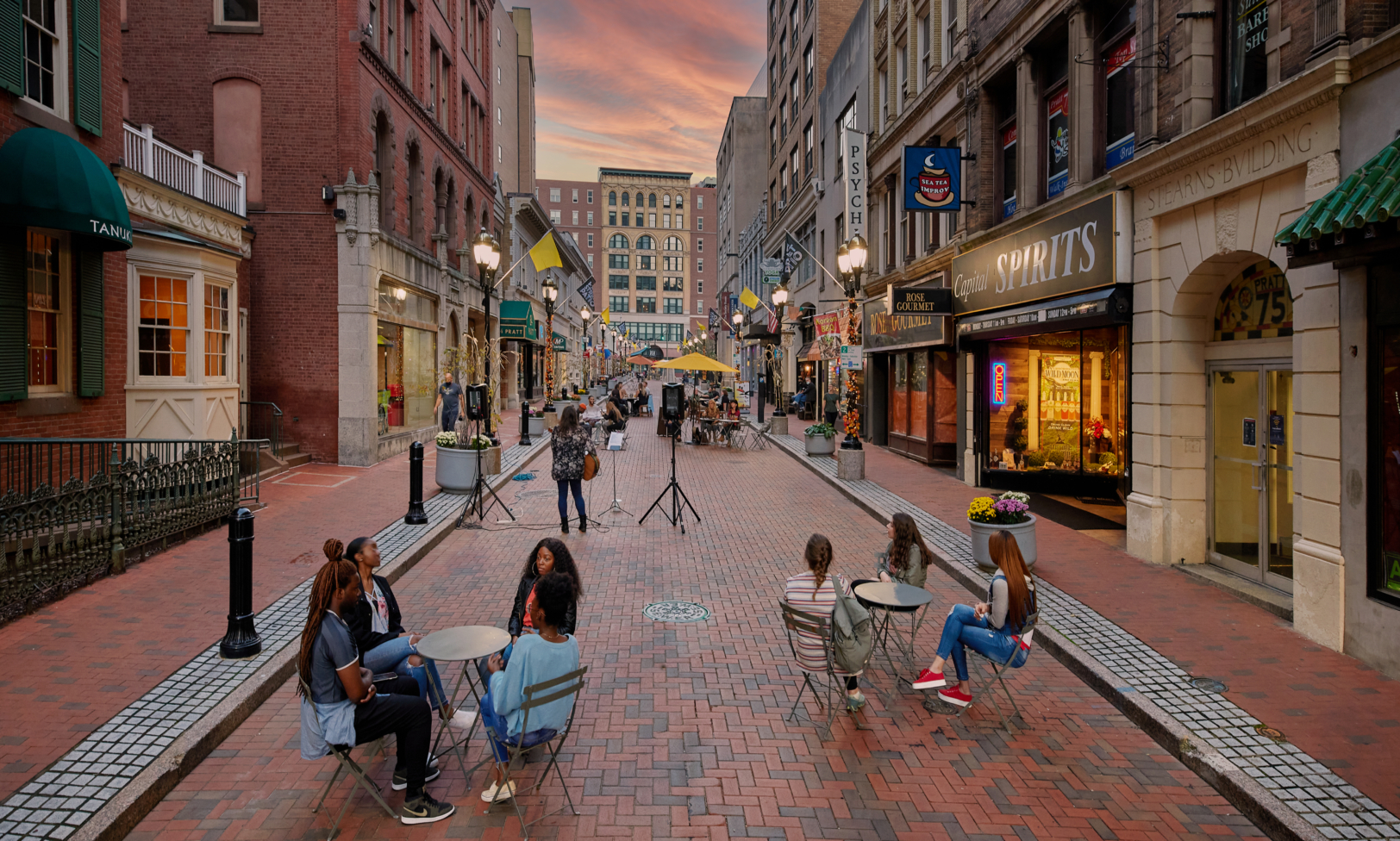 Pratt Street at dusk with a musician and several tables of people enjoying the atmosphere.