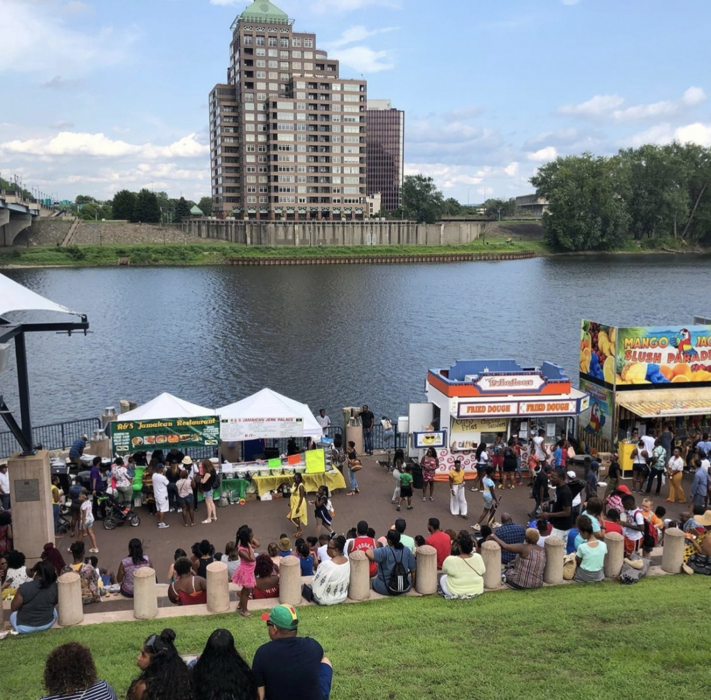 People sitting along the Connecticut River at a Festival