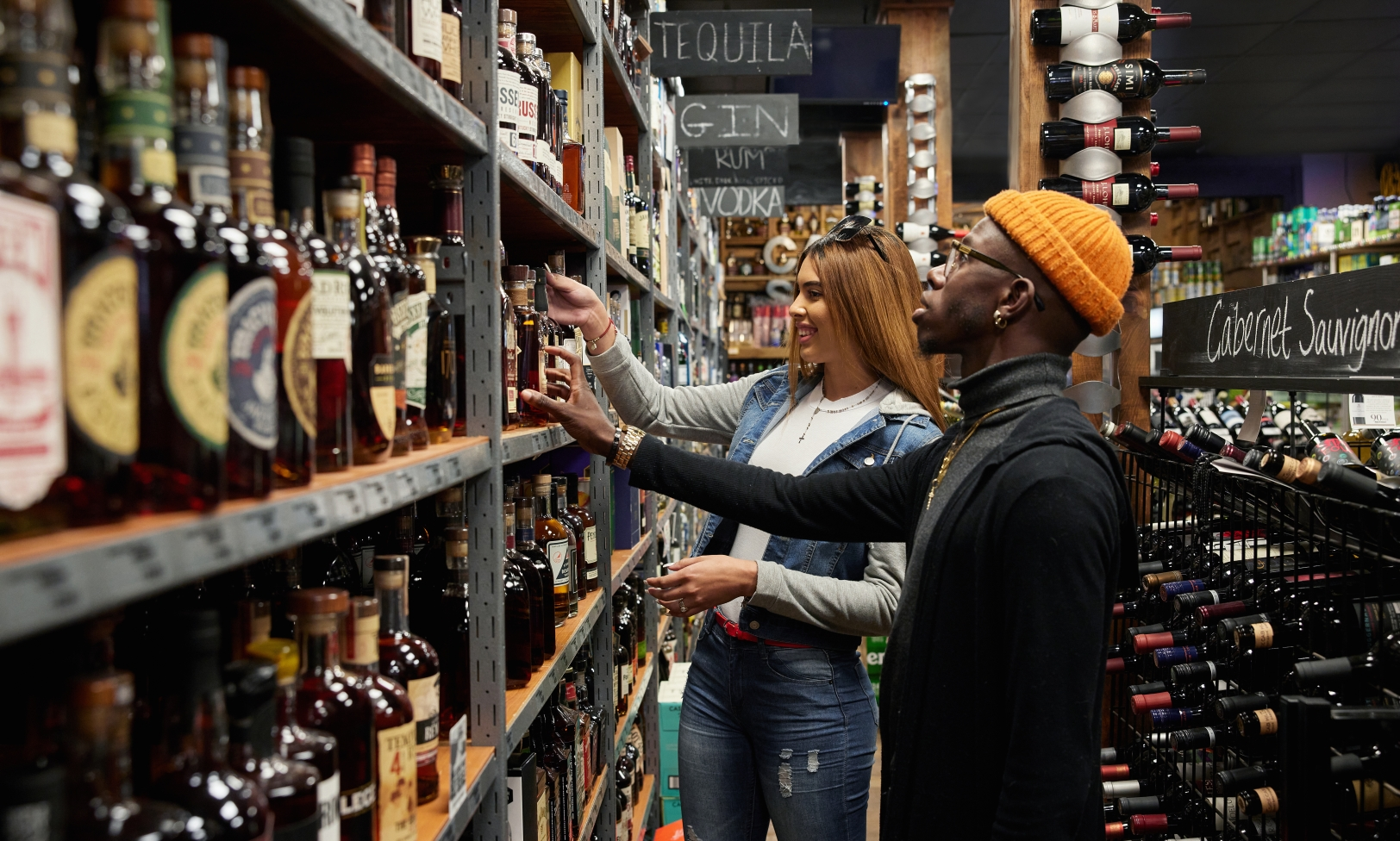 Two people browse shelves of liquor bottles at Capital Sprits