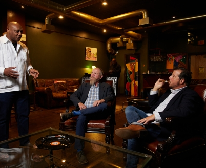 Gerry Grate, owner of the Tobacco Shop, talks to two patrons about cigars.