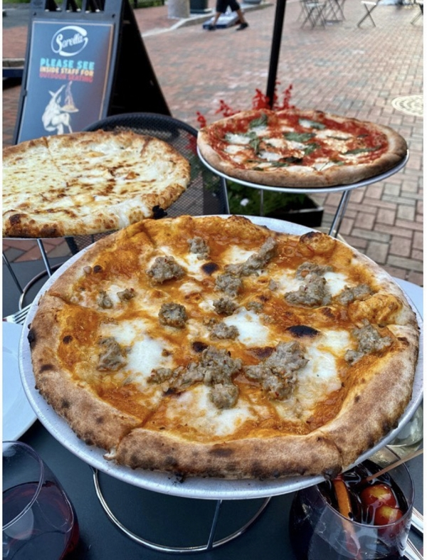 Three pizzas with varying toppings on an outdoor table on Pratt Street