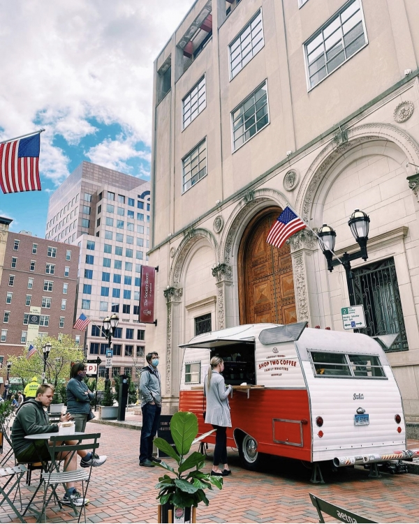 People shopping at a old fashioned station wagon parked on Pratt Street for a popup event.