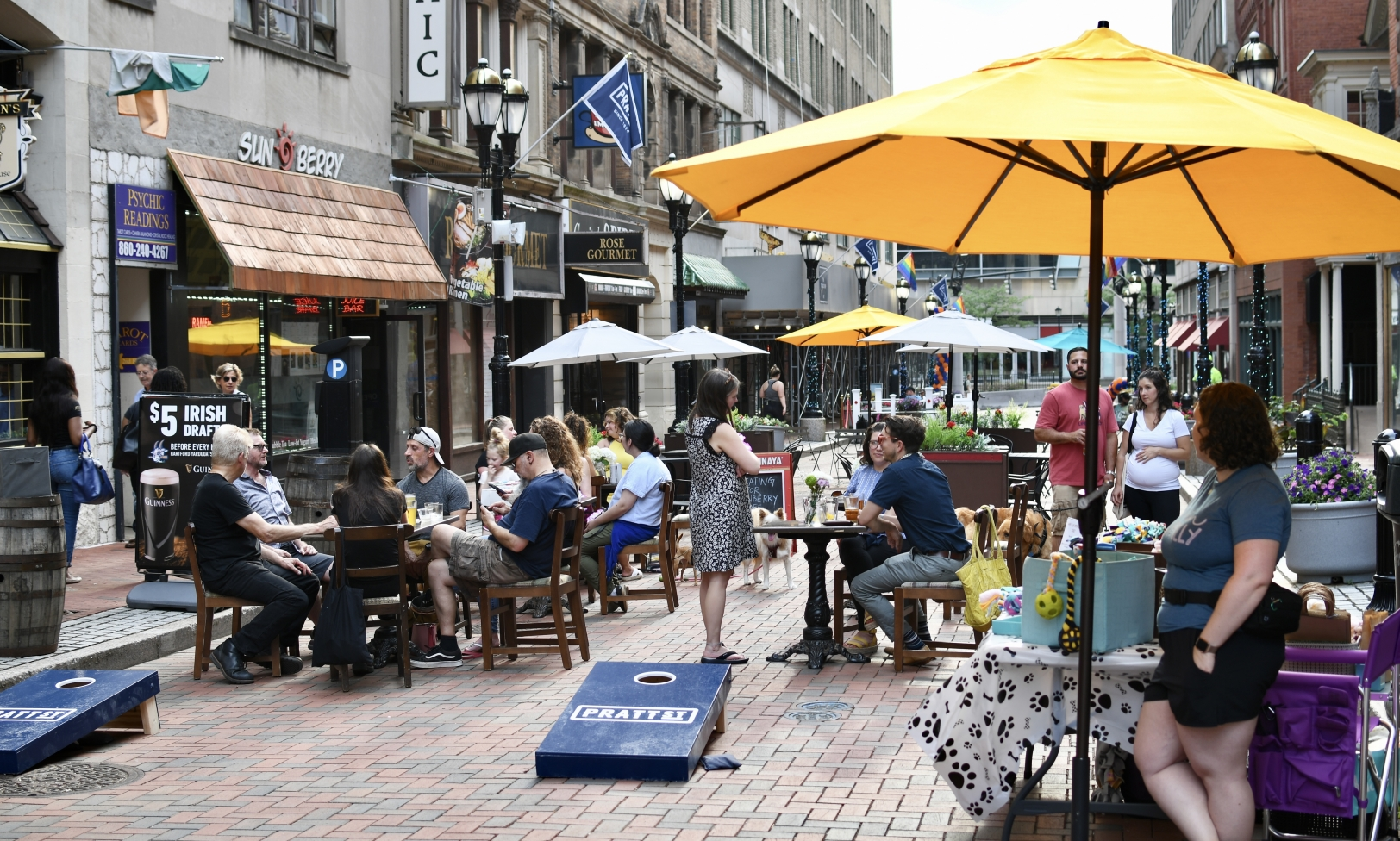 People sitting at tables on Pratt Street with cornhole boards in the foreground.