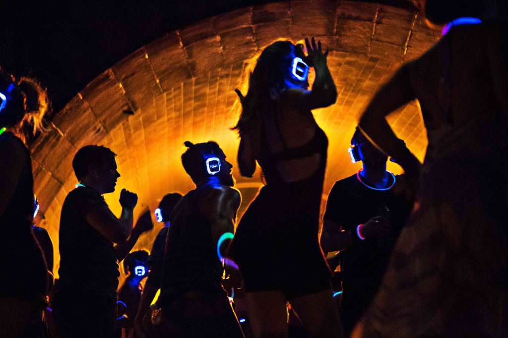 People dancing in a dark tunnel during an evening silent disco