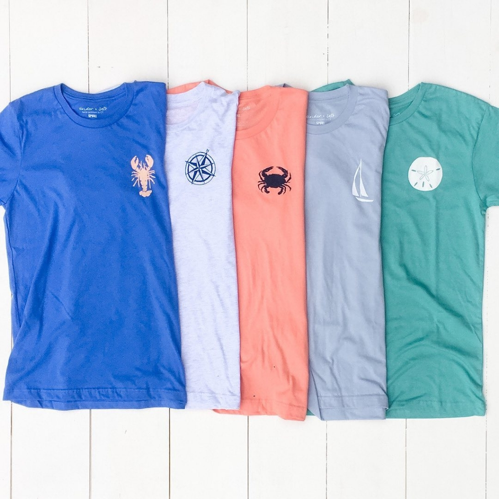 A variety of t shirts with nautical icons on the upper left side.