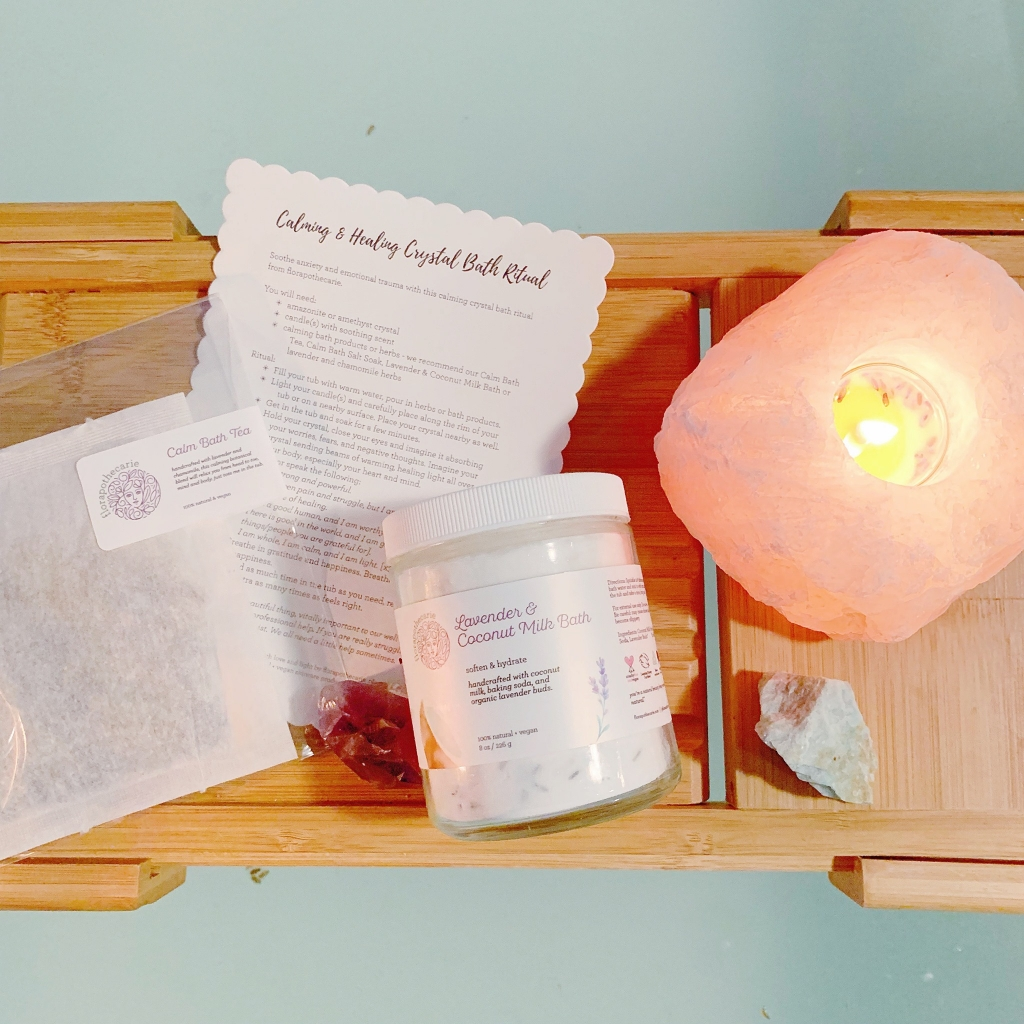 A wooden tray with a salt lamp and jar of skincare product and accompanying paper materials.