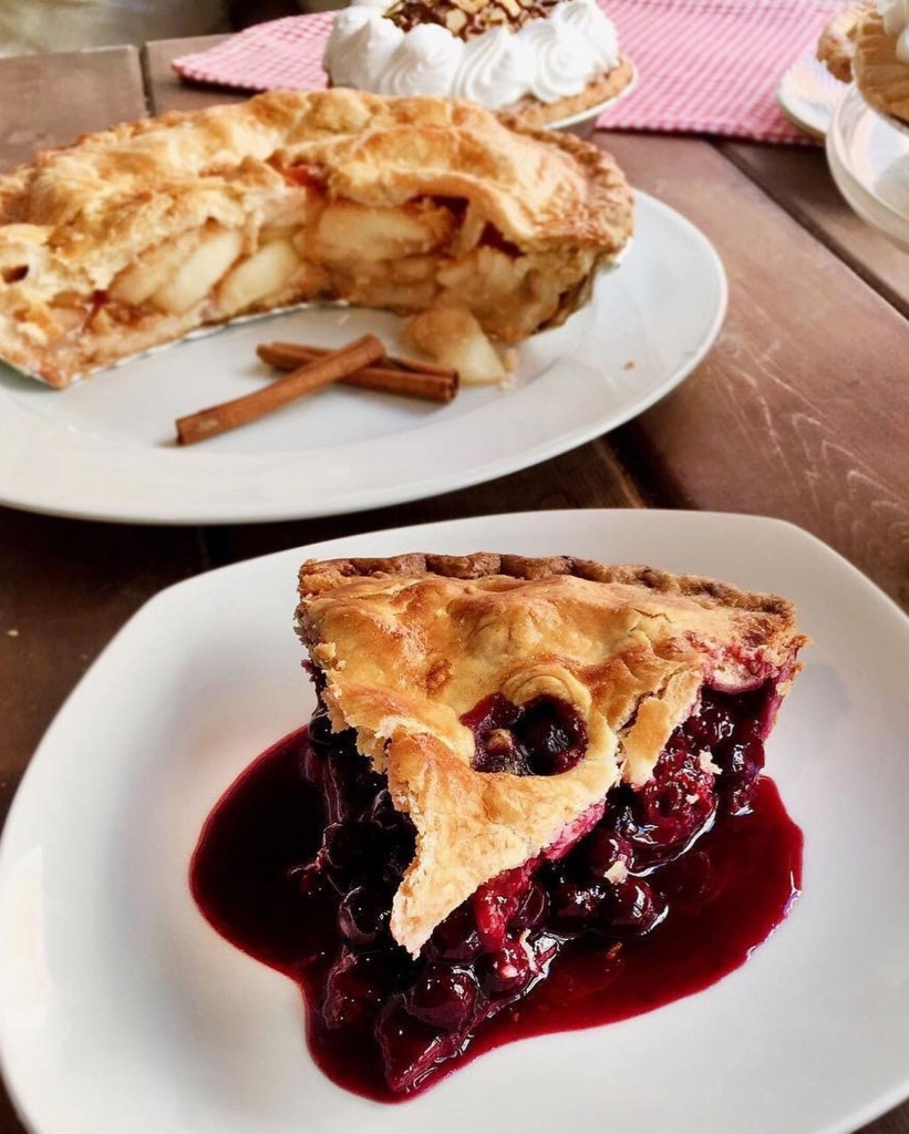 A slice of berry pie with a slice of pie in the background.