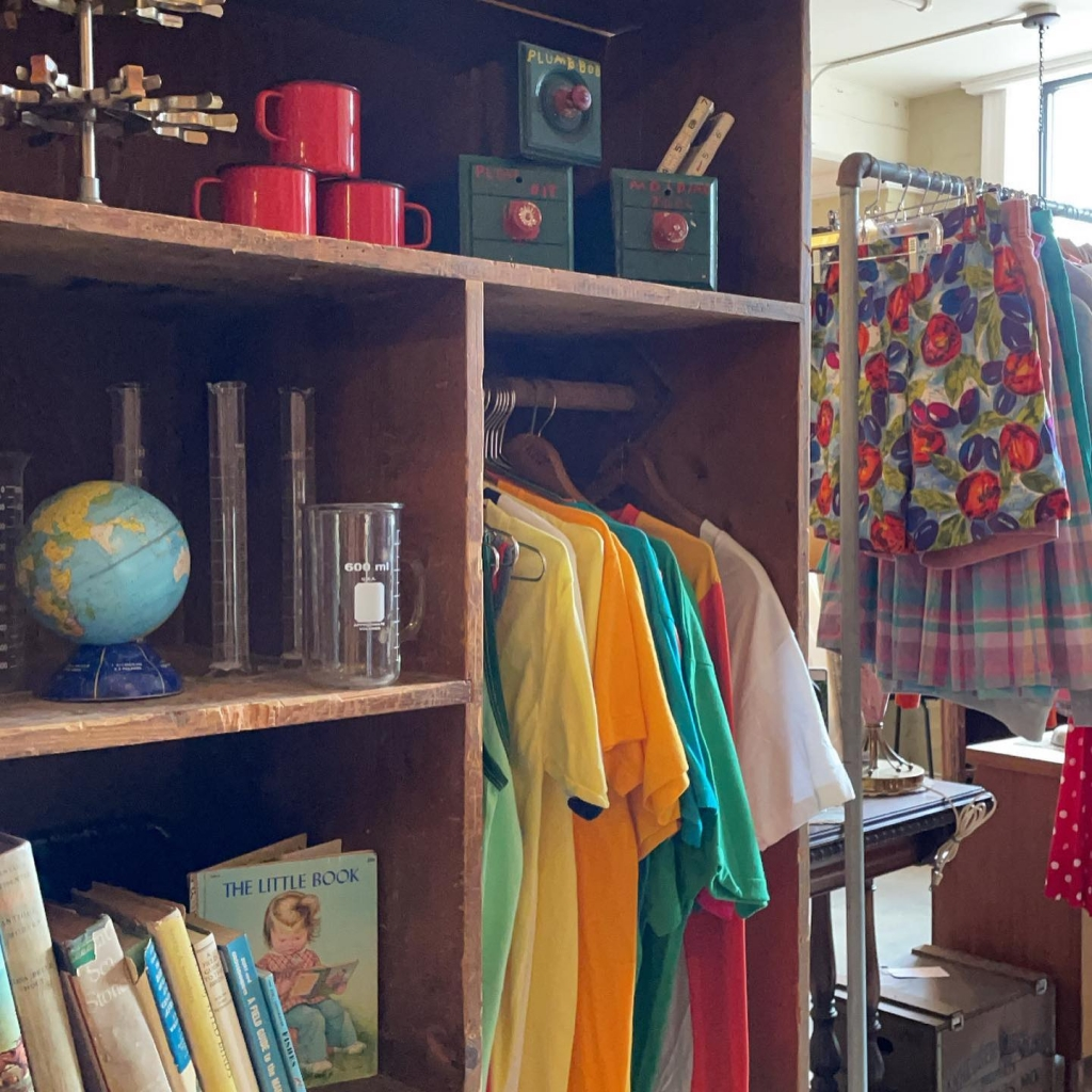 Racks of clothes and shelves with vintage decor items.