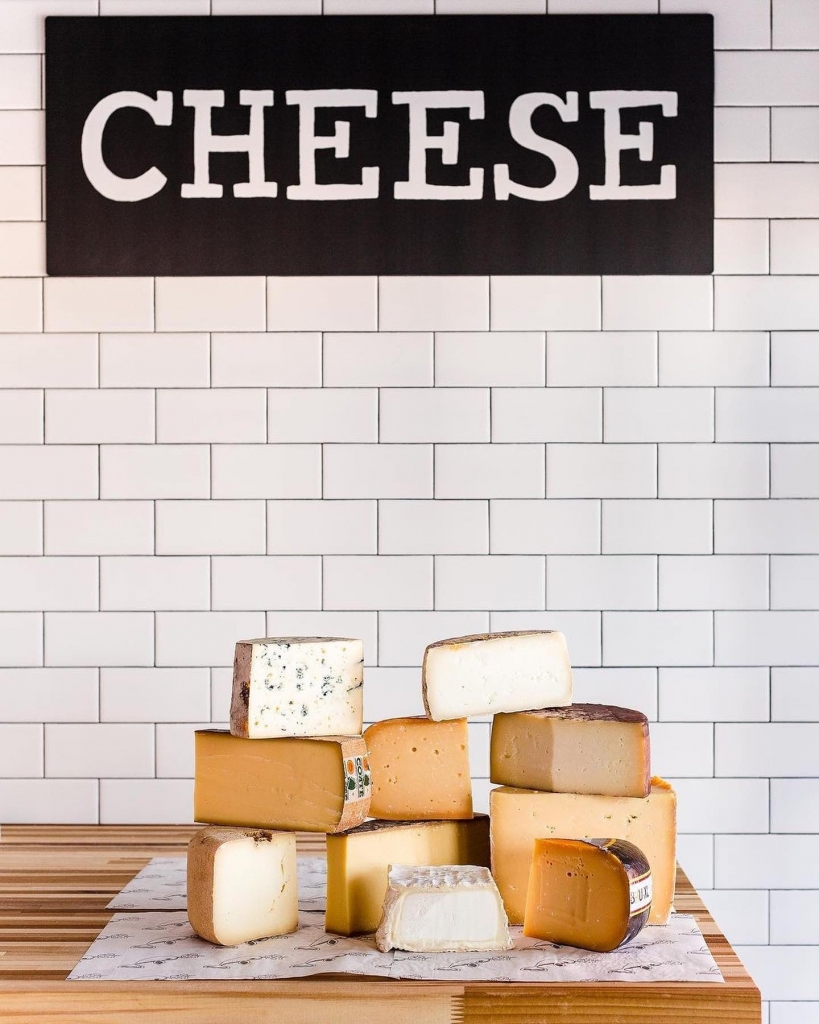 """Various blocks of cheese in front of a sign saying """"cheese"""""""