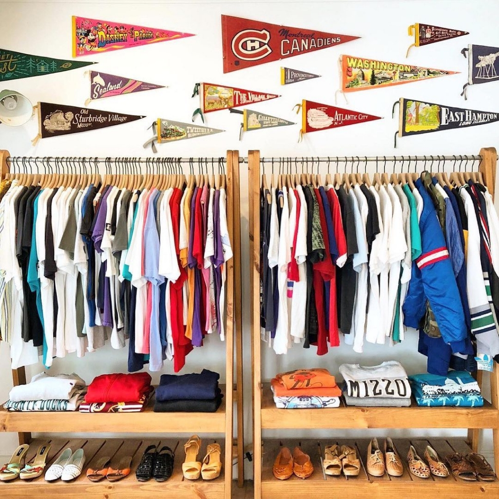 A rack of t shirts of various colors with vintage university pendants and vintage shoes.
