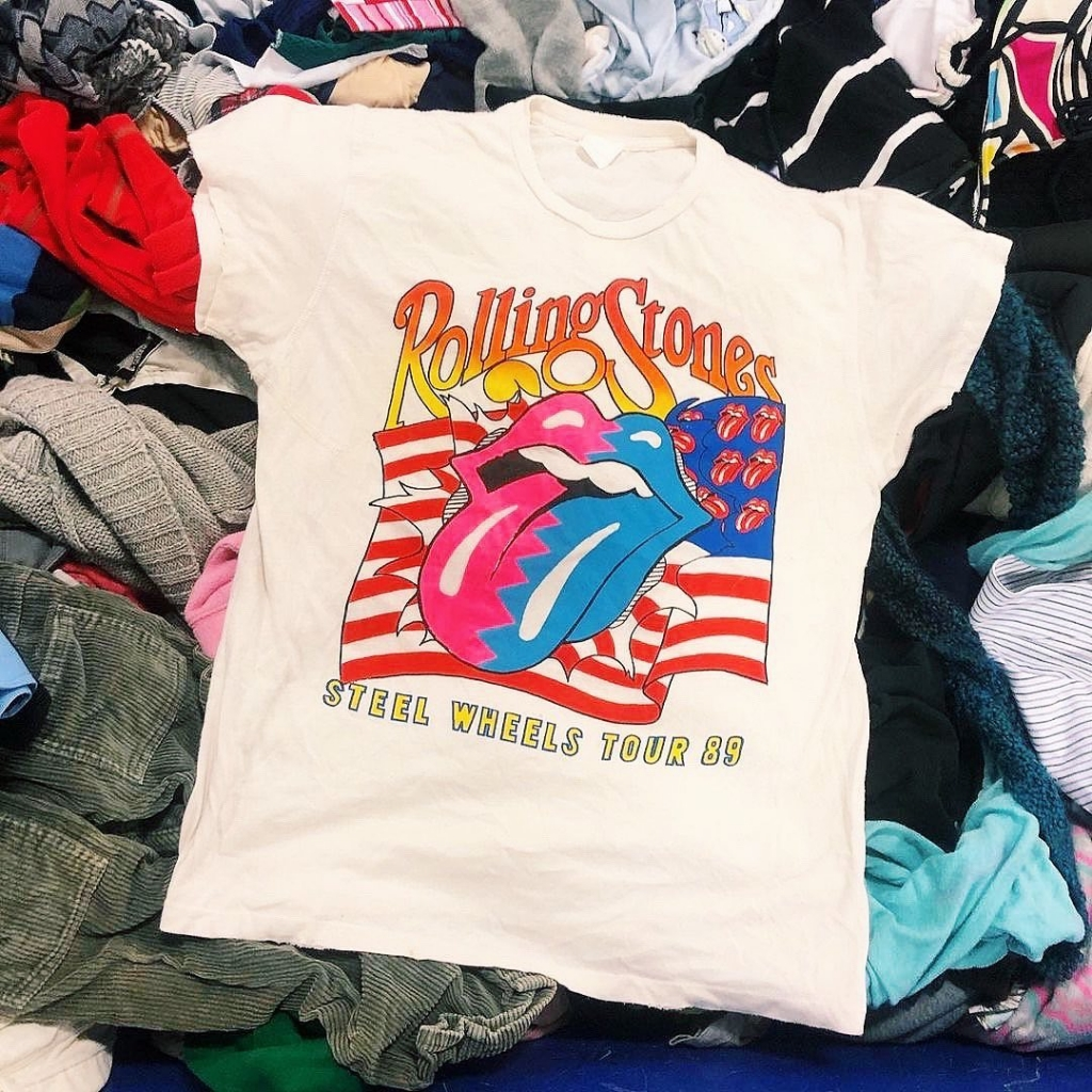 Rolling Stones band tee on a pile of t shirts.