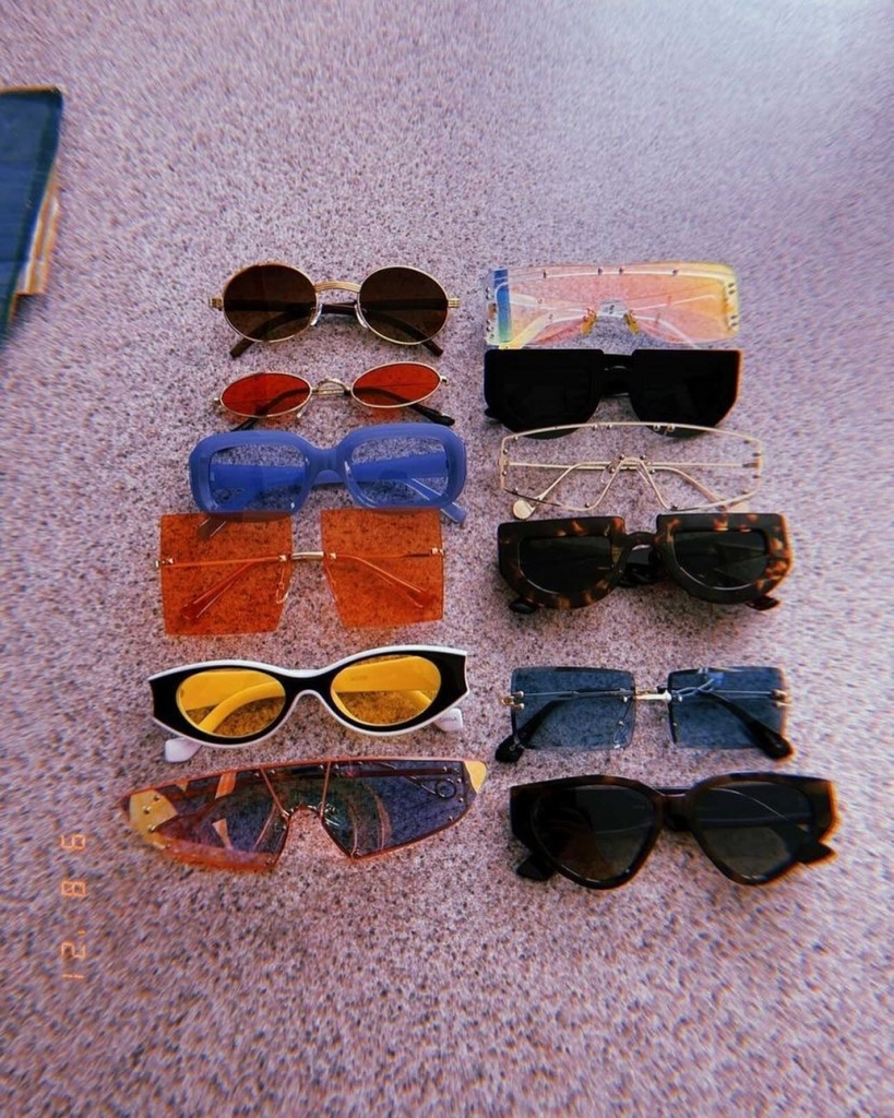 Twelve pairs of trendy sunglasses with smaller frames in a variety of colors.